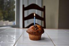 En födelsedagmuffin med stearinljuset arkivbild