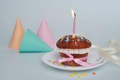En födelsedagmuffin, muffin med stearinljuset, på Grey Blue bakgrund Rosa färgpilbåge Isoalted Stearinljus Royaltyfria Bilder