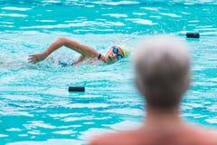 En förälder som håller ögonen på en ung kvinnlig simmaresimning i fristil a Royaltyfri Fotografi