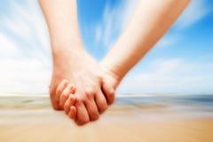En förälskad hand för par - in - hand på den soliga stranden Arkivbild