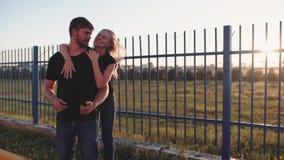 En förälskad omfamning för attraktiva par och att tycka om ett intimt ögonblick tillsammans, mot solnedgången eller soluppgången lager videofilmer