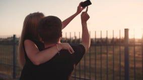 En förälskad omfamning för attraktiva par och att tycka om ett intimt ögonblick tillsammans, mot solnedgången eller soluppgången arkivfilmer