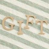 En ` för ord`-GÅVA på tygbakgrund arkivbild