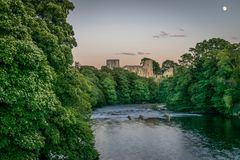 En fördärva av en slott som sticker fram till och med en skog bredvid en flod med en måne royaltyfria bilder