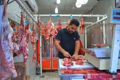 En försäljare klipper delar av kött, Bandar Abbas, Hormozgan, Iran Royaltyfria Foton