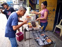 En försäljare säljer en variation av grillfester på pinnen i den Antipolo staden, Filippinerna royaltyfri fotografi