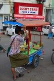 En försäljare som bär den traditionella Burmese longyien som säljer nya & inlagda frukter i hans rörliga stall arkivbild
