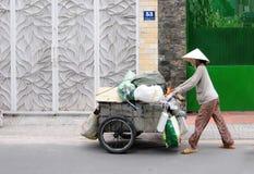 En försäljare som går på gatan på centret i ton, Vietnam Royaltyfria Bilder