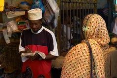 En försäljare som tar en anmärkning på en afrikansk marknad royaltyfri fotografi