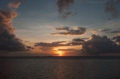 En försiktig solnedgång på havet: den orange bollen av solen sitter över horisonten, grå färg som massiva moln är upplysta vid en Arkivfoto