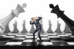 En förskräckt affärsman står mellan en svart och ett vitt schack gör till kung att falla på honom royaltyfri foto