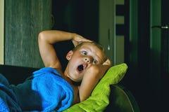En förskräckt pojke i säng på natten Skräck för barn` s arkivbilder