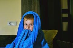 En förskräckt pojke i säng på natten Skräck för barn` s arkivbild