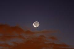 En försvagas Crescent Moon spelar med moln på gryning Arkivbilder