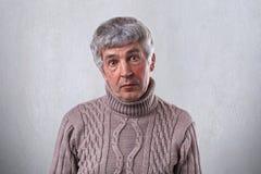 En förvånad gamal man med mörka ögon som har skrynklor på hans framsida och grå färghår som bär den bruna tröjan som ser direkt i Royaltyfri Foto