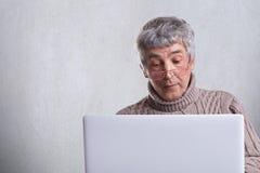 En förvånad iklädd tröja för hög man som har gråa hår och skrynklor genom att använda hans bärbar dator som surfar i internet En  Royaltyfri Fotografi