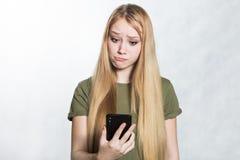 En f?rbryllad och bekymrad ung kvinna som rymmer en smartphone som ser med ett f?rv?nat uttryck royaltyfri foto