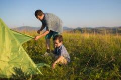 En fader med hennes son ställde tillsammans in tältet Royaltyfri Fotografi