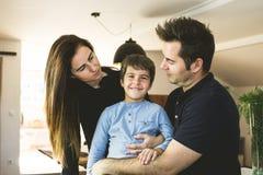 En fader och en moder som hemma kramar deras son Koppla ihop uppvisning av affektion till deras son Förälskelse mellan föräldrar  arkivfoto