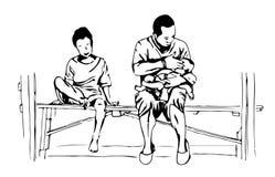 En fader som rymmer en behandla som ett barn i hans arm och en ung pojke sitter på en bänk Arkivfoton