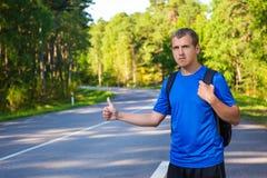 En faisant de l'auto-stop le voyageur essayez d'arrêter la voiture sur le chemin forestier Photos libres de droits