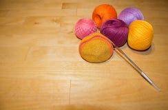 En faisant du crochet le coton en cours et coloré filetez les boules sur le fond en bois avec l'espace Image libre de droits