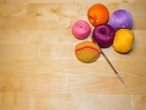 En faisant du crochet le coton en cours et coloré filetez les boules sur le fond en bois avec l'espace Photo libre de droits