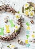 En faisant la guirlande faite maison de Pâques des vignes avec des fleurs, empaquetez les lapins, rubans sur un fond blanc, vue s Photo stock