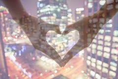 En faisant le coeur signez avec des mains, vue de nuit, double exposition Images libres de droits