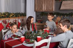 En familj av fours på festliga nytt års tabell som talar för att ha gyckel, sonen, häller te från kokkärlet fotografering för bildbyråer
