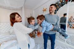 En familj av fyra som framme kramar av julträdet förälskelse, lycka och stort familjbegrepp royaltyfria foton