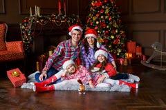 En familj av fyra som framme kramar av julträdet på sängen Helgdagsafton för ` s för nytt år lycka och stort familjbegrepp fotografering för bildbyråer