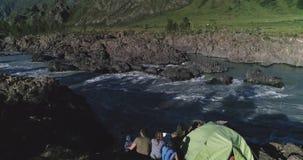 _ En familj av handelsresande med barn sitter nära ett tält och tycker om en sikt av de bergfloden och bergen stock video