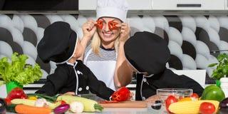 En familj av kockar äta som är sunt Den lyckliga familjmodern och barn förbereder grönsaksallad i kök royaltyfria foton