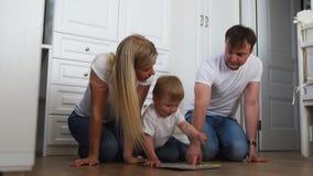 En familj av tre i vita T-tröja och jeans som sitter på golvet av deras sovrum som spelar med pojken in stock video