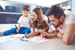 En familj drar på papper som ligger på deras fria tid på golvet fotografering för bildbyråer