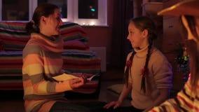 En familj framlägger deras gåvor, medan sitta under ett julträd lager videofilmer