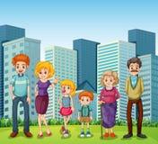 En familj framme av de högväxta byggnaderna i staden Royaltyfri Bild