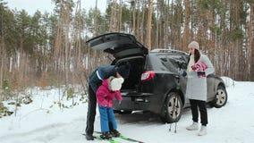 En familj med ett barn spenderar rolig tid i natur Familjferie i vinterskogen arkivfilmer
