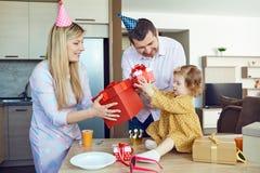 En familj med en kaka gratulerar ett lyckligt barn på hans födelsedag royaltyfria foton