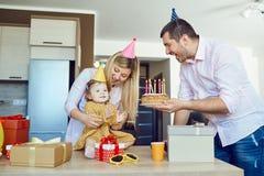 En familj med en kaka gratulerar ett lyckligt barn p? hans f?delsedag royaltyfri bild