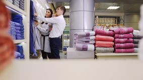 En familj på shopping En familj som söker efter badrockar, medarbetare kommer och sätter en bunt av handdukar framme av kameran stock video