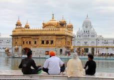 En familj som framme ber av det guld- tempelet Royaltyfria Bilder