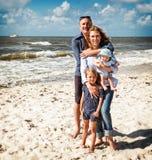 En familj som omfamnar på stranden Fotografering för Bildbyråer