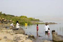 En familj som paddlar i vattnet på den västra kusten av havsnollan royaltyfri foto