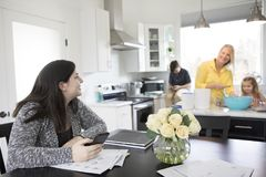 En familjbakning och en spenderatid tillsammans i deras moderna kök arkivfoton