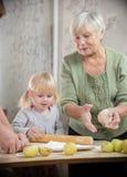 En farmor och en sondotter gör små pajer arkivfoton
