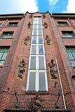 En fasad av en byggnad med röda tegelstenar och statyer i berlin royaltyfri fotografi
