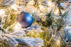 En fast blå julprydnad på en flockas julgran royaltyfria bilder