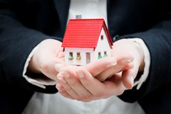 En fastighetsmäklare som rymmer ett litet nytt hus i henne händer Arkivfoto